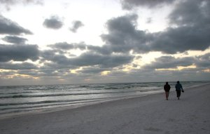 9816-a-couple-walking-on-the-beach-under-a-cloudy-sunset-pv